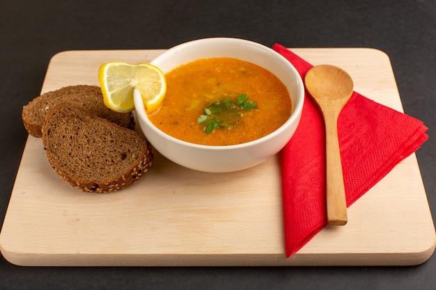 暗い机の上にレモンスライスとパンの塊が付いたプレート内のおいしい野菜スープの正面図。