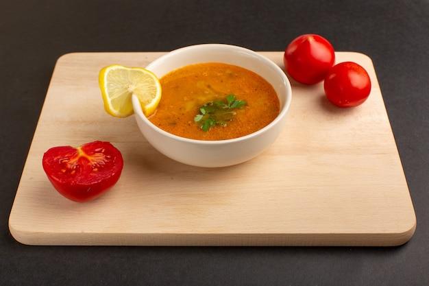 暗い机の上にレモンスライスと赤いトマトが入ったプレートの内側の正面図のおいしい野菜スープ。