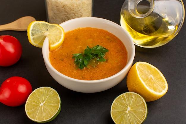 暗い机の上にレモンスライスオイルと赤いトマトが入ったプレート内のおいしい野菜スープの正面図。