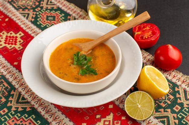 Вид спереди вкусный овощной суп внутри тарелки с помидорами и лимоном на темном столе.