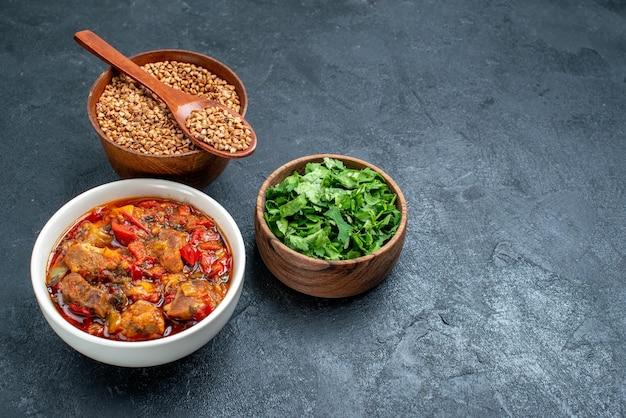 Vista frontale gustosa zuppa di verdure con grano saraceno crudo sullo spazio grigio