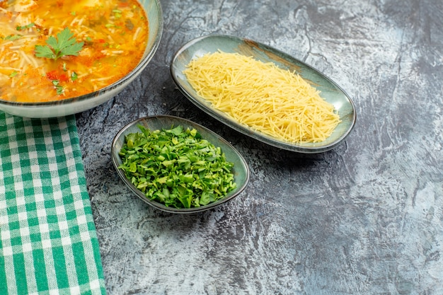 Front view tasty vermicelli soup with greens and raw vermicelli on a light-grey background warm pasta dough food dish sauce potato photo