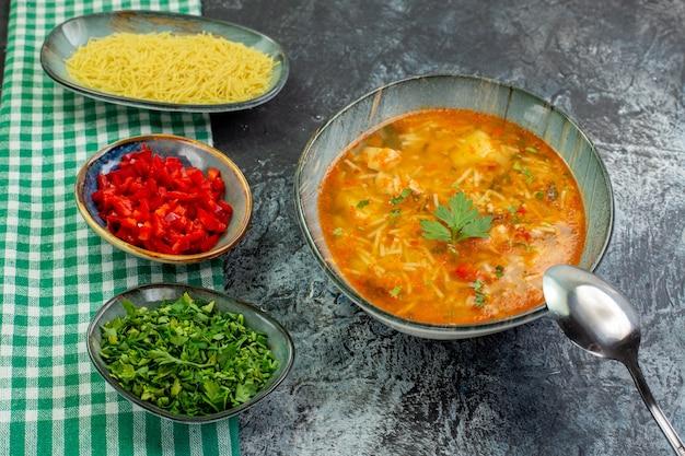 正面図薄灰色の背景にスライスしたピーマンと緑のおいしい春雨スープポテトフード生地皿パスタソース写真