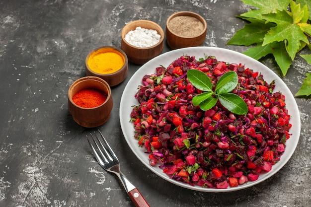 Vista frontale gustosa insalata di barbabietole vinaigrette con fagioli su sfondo scuro
