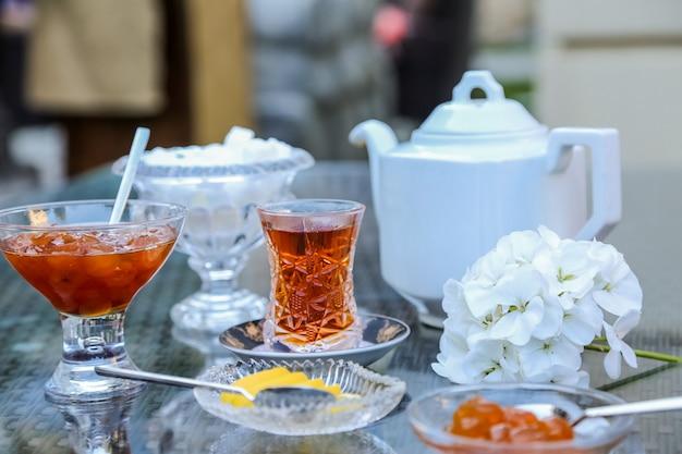 Vista frontale del tè in vetro armudu con marmellata di ciliegie bianche e spicchi di limone sul tavolo