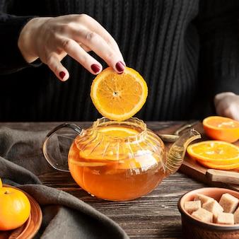 Vista frontale del concetto del tè con la fetta arancio