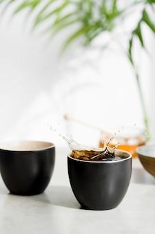 Вид спереди, брызги чая в чашке