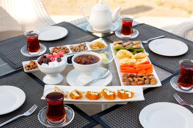 Una tabella di tempo di vista frontale con marmellata, marmellata, noci, dolci e caramelle nel ristorante durante il giorno, tavolo da tè dolce all'esterno
