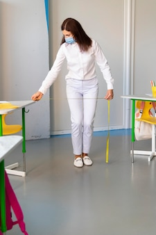 Front view teacher measuring the distance between desks