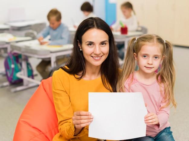 Учитель вид спереди показывает пустой лист бумаги