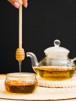 正面のティーポットと瓶の上に蜂蜜ディッパーを持っている手