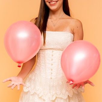 Front view teenage girl holding birthday balloons