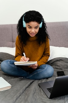 Vista frontale dell'adolescente che utilizza computer portatile per la scuola in linea