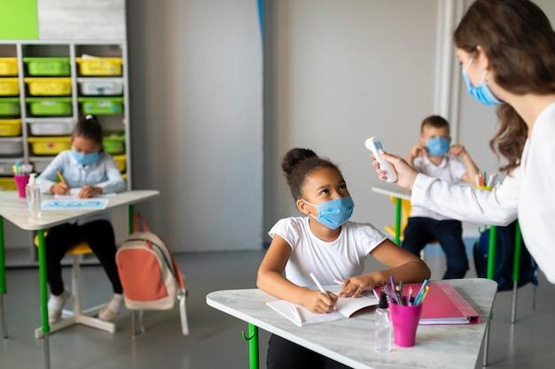 Misurazioni della temperatura vista frontale in classe durante la pandemia