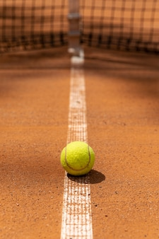 Front view tennis ball on court ground