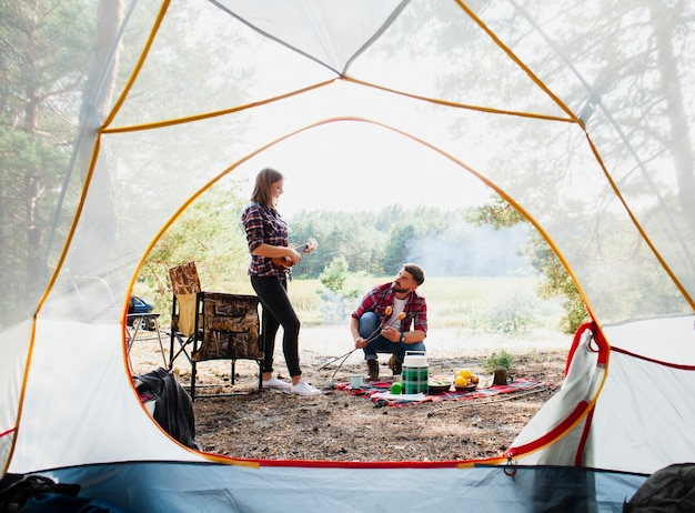 Front view tent and couple cooking
