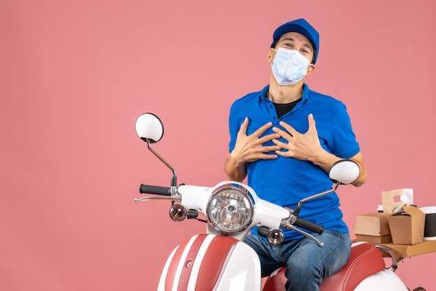 Vista frontale del corriere grato uomo in maschera medica che indossa cappello seduto su scooter che consegna ordini su sfondo pesca pastello pastel