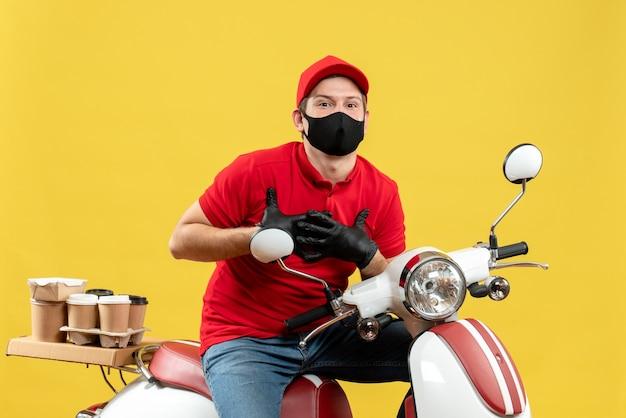 Vista frontale del corriere grato uomo che indossa camicetta rossa e guanti cappello in maschera medica consegna ordine seduto su uno scooter