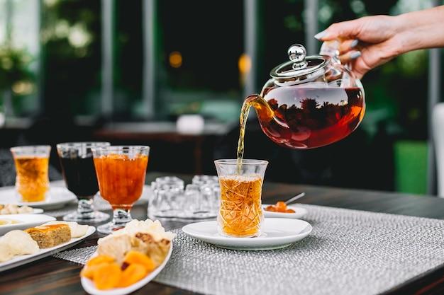 Вид спереди девушка наливает чай из чайника в бокал armoud с вареньем и сладостями на столе