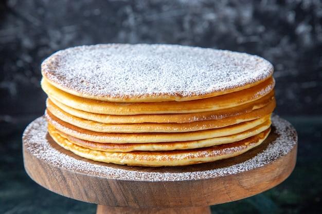 둥근 나무 보드 어두운 표면에 설탕 가루와 전면보기 얇은 케이크 층