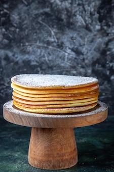 丸い木の板の暗い表面に砂糖粉が付いている正面図の薄いケーキの層