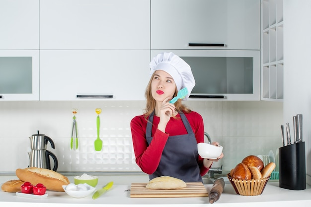 Front view thinking blonde woman in cook hat and apron buttering bread in the kitchen