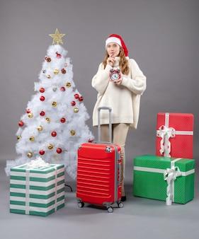 Donna bionda di pensiero di vista frontale con il cappello della santa che tiene sveglia rossa vicino all'albero e ai regali bianchi di natale
