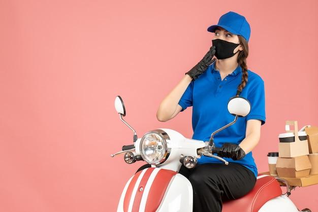 Vista frontale della ragazza del corriere pensante che indossa maschera medica e guanti seduti su uno scooter che consegna ordini su sfondo color pesca pastello
