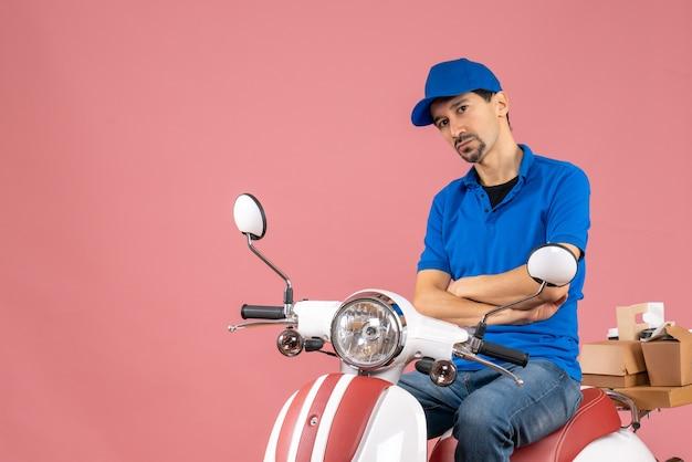 Vista frontale del corriere pensante che indossa un cappello seduto su uno scooter su sfondo color pesca pastello