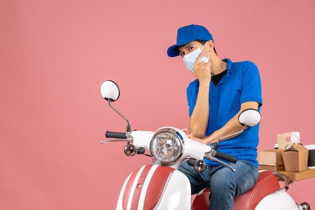 Vista frontale dell'uomo pensante corriere in maschera medica che indossa cappello seduto su scooter su sfondo pesca pastello