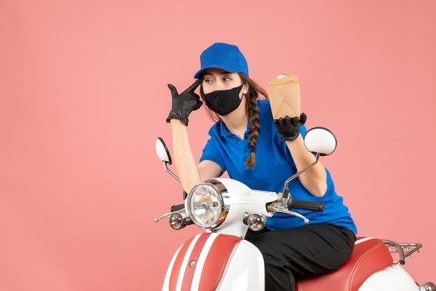 Vista frontale del fattorino pensante che indossa maschera medica e guanti seduto su scooter che consegna ordini su sfondo pesca pastello