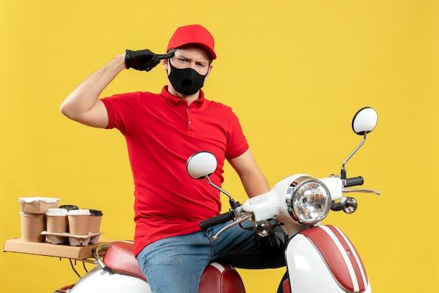 Vista frontale del pensiero emotivo giovane adulto che indossa guanti camicetta e cappello rossi in mascherina medica offrendo ordine seduto su scooter su sfondo giallo