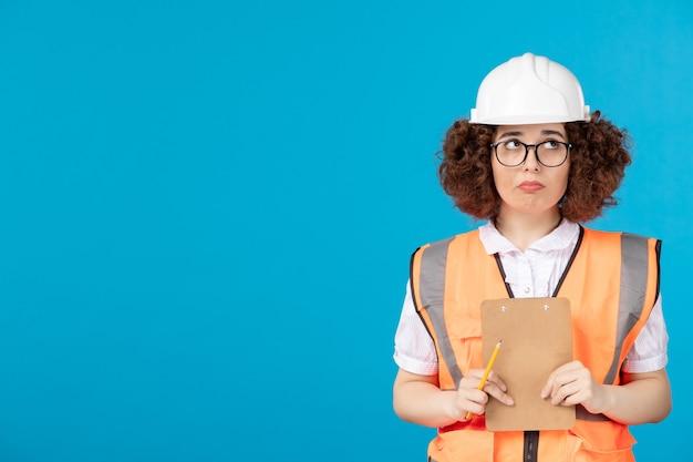 青い壁に制服を着た女性ビルダーを考える正面図