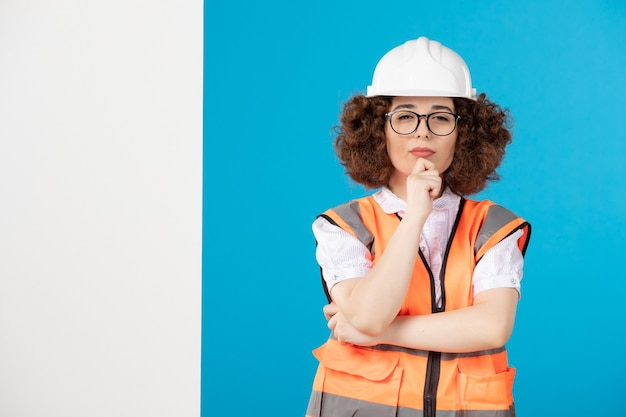 Front view thinking female builder in uniform on a blue wall