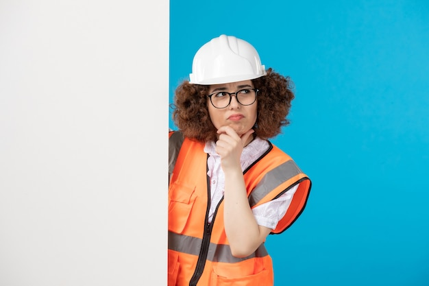 Front view thinking female builder in uniform on blue wall