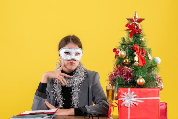 Ragazza di pensiero di vista frontale con la maschera che si siede al tavolo che mette il dito