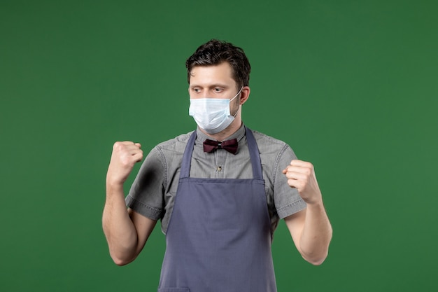 Vista frontale del cameriere del ragazzo pensante in uniforme con maschera medica sul muro verde