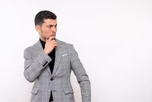 白い孤立した背景に立っているスーツのハンサムな男性を考える正面図