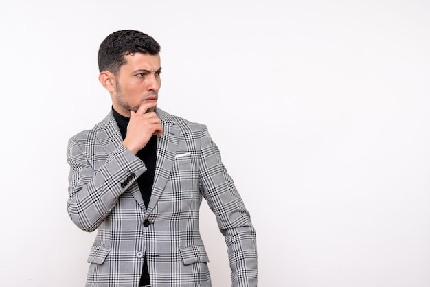 Front view thinking handsome male in suit standing on white isolated background