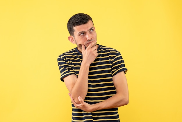 Front view thinking handsome man in black and white striped t-shirt yellow isolated background