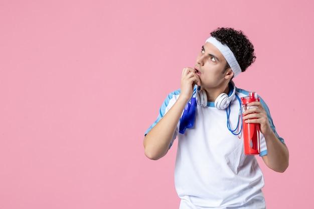 Вид спереди мышления спортсмена в спортивной одежде с бутылкой воды