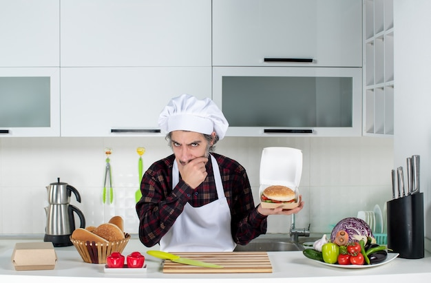 Front view thinking male chef holding up burger in modern kitchen