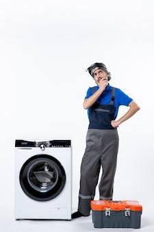 Vista frontale del riparatore pensante in piedi vicino alla borsa degli attrezzi della lavatrice sul muro bianco