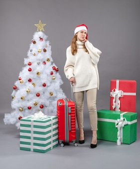 Вид спереди думающая женщина, держащая красный чемодан