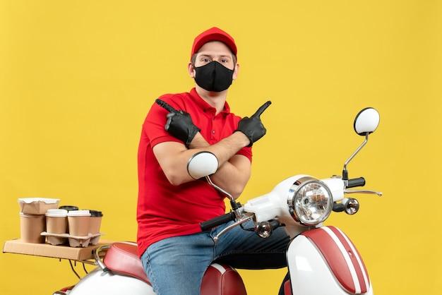 Vista frontale del giovane adulto di pensiero che indossa la camicetta rossa e guanti del cappello nella mascherina medica che consegna l'ordine che si siede sullo scooter che indica entrambi i lati su fondo giallo