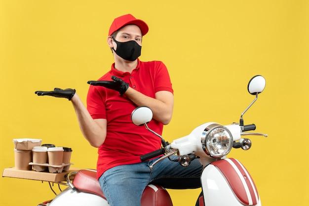 Vista frontale del giovane adulto di pensiero che indossa la camicetta rossa e guanti del cappello nella mascherina medica che consegna l'ordine che si siede sullo scooter che indica qualcosa sul lato destro su priorità bassa gialla