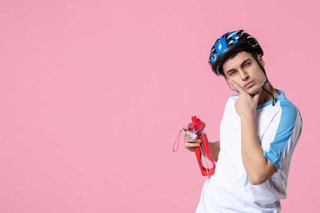 Вид спереди мышления молодого спортсмена в шлеме спортивной одежды и держащего бутылку воды