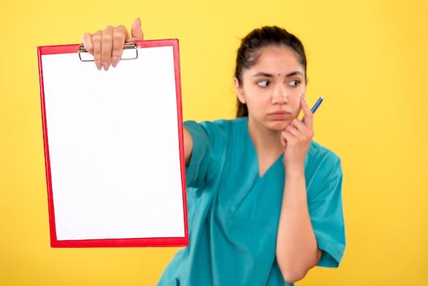 黄色の背景にクリップボードを保持している若い女性を考える正面図
