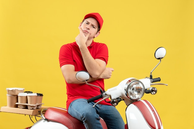 Front view of thinking young guy wearing red blouse and hat delivering orders on yellow background