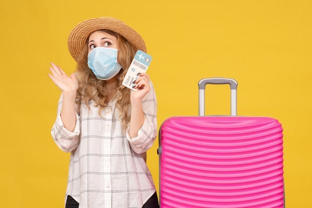 Vista frontale del pensiero giovane donna che indossa la maschera che mostra il biglietto e in piedi vicino alla sua borsa rosa guardando il giallo